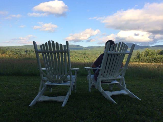 Johanne sur une chaise de méditation face aux montagnes de Sutton.