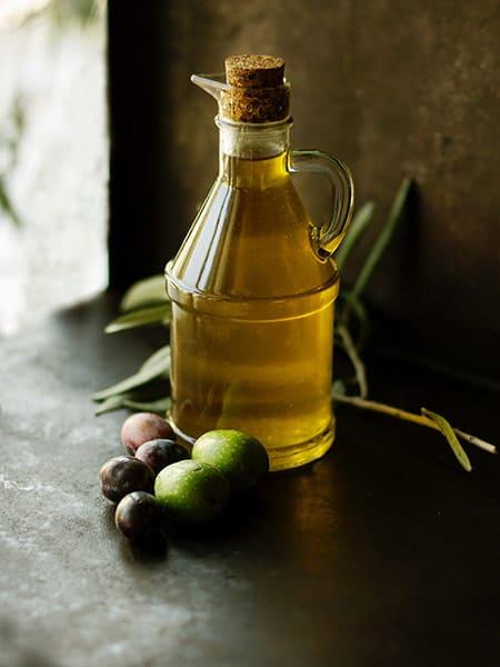 Bouteille d'huile d'olive sur surface foncée avec quelques olives