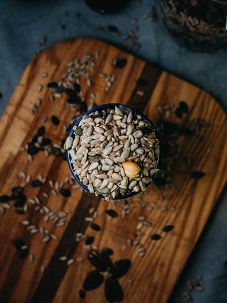 Pot de graines de tournesol sur planche à découper en bois