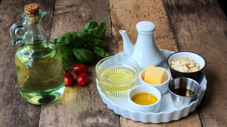 Différentes huiles présentées dans des pots ou bocaux divers sur planche de bois