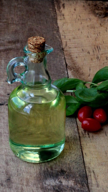 Bouteille d'huile transparente avec bouchon en liège sur planche de bois avec tomates et verdure