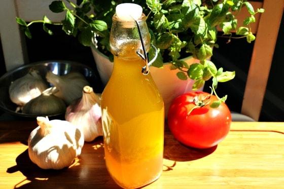 Bouteille de la vinaigrette maison à 4 ingrédients avec ail et tomate au soleil.