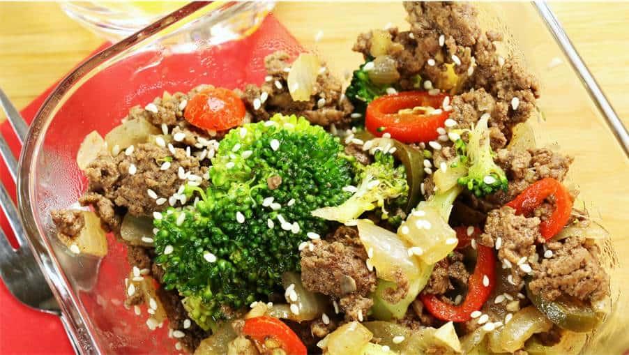 Vue de haut d'un bol de boeuf au gingembre avec brocoli, piments et sésame.