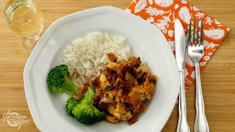 Assiette blanche d'émincé de poulet avec brocoli et riz, accompagné d'un verre de vin blanc sur planche de bambou