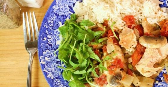 Assiette bleue avec du poulet chasseur sans lactose, de la roquette et du riz blanc