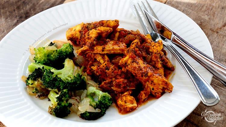 Succulent émincé de poulet aux tomates avec du brocoli aux oignons dans une assiette avec ustensiles