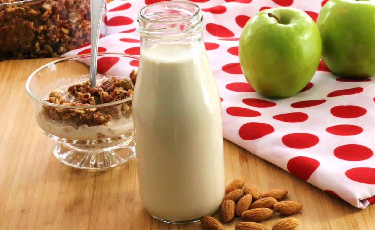 Photo d'une bouteille avec du lait d'amandes devant un bol de granola et de pommes vertes.