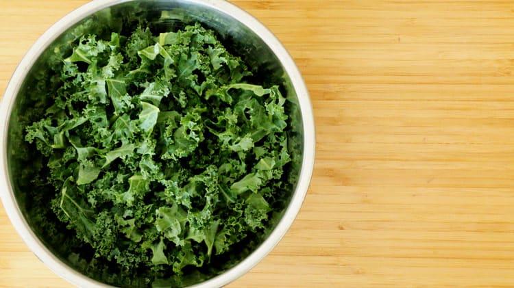 Chou frisé kale coupé en morceau, tiges enlevées dans un bol en stainless, sur une planche de bois