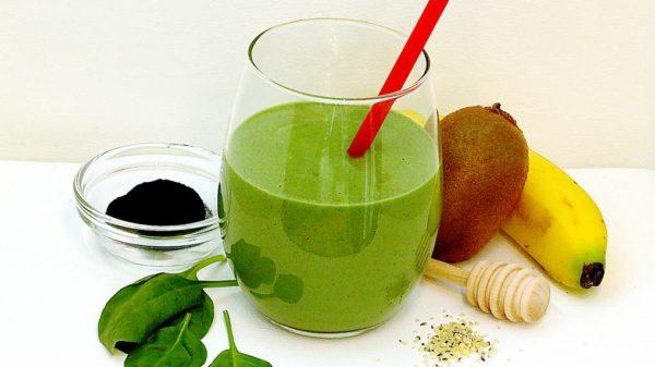 Smoothie vert avec kiwi, spiruline, banane, épinards, miel et graines de chanvre décortiquées.