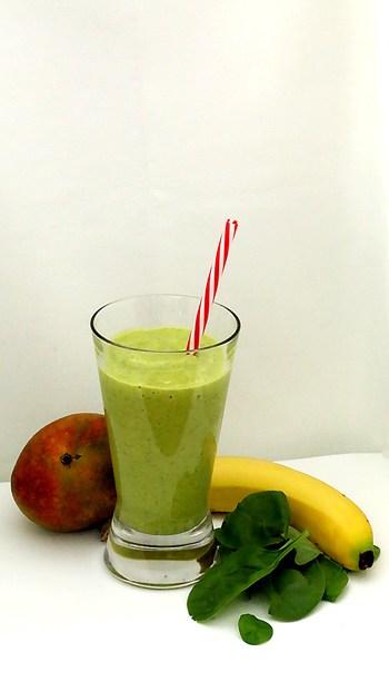 Verre de smoothie vert crémeux tropical avec une banane, des épinards et une mangue