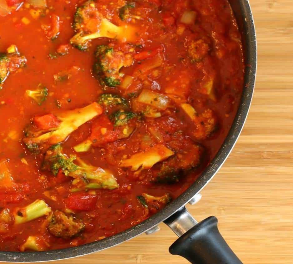 Dans un grand poêlon on y voit la sauce tomate maison sur planche de bambou