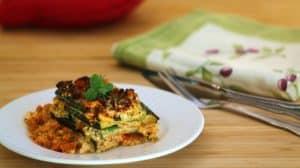 Portion de lasagne sur assiette blanche sur planche de bois pâle