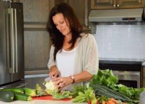 Johanne Gilbert dans sa cuisine qui coupe un chou-fleur et plusieurs autres légumes sont sur le comptoir.