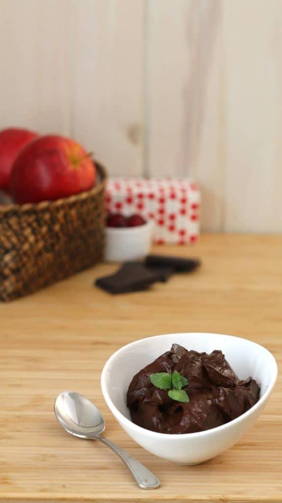 Mousse au chocolat au lait sans lactose dans un bol sur planche de bois.
