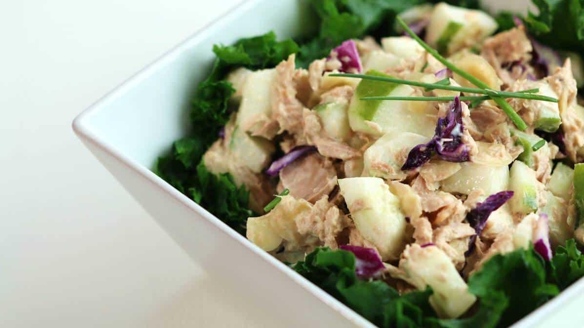 Bol carré blanc avec une salade de thon et gingembre sur lit de kale cuit vapeur.