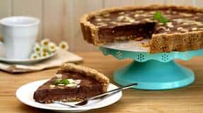 Assiette de tarte à la ganache au chocolat avec pointe coupée dans une assiette blanche.