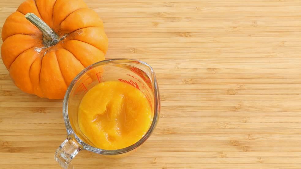 Une tasse à mesure avec de la purée de citrouille et une petite citrouille à cuire sur planche de bois.