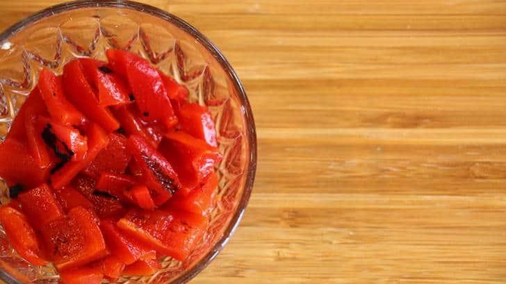 Bol de poivrons rouges sur planche de bois, vu de haut.