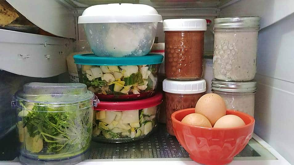 Photo de quelques salades, oeufs cuits durs et pudding de chia préparés à l'avance dans le réfrigérateur.