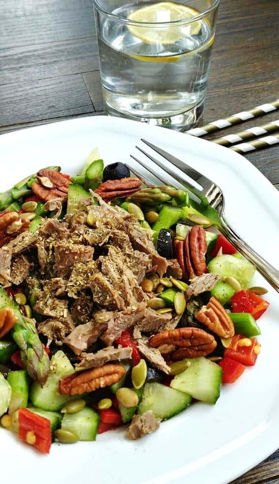 Bol de salade de canard aux asperges vertes avec un verre d'eau et tranche de citron, sur fond de bois foncé avec des pailles rayées blanches et or.