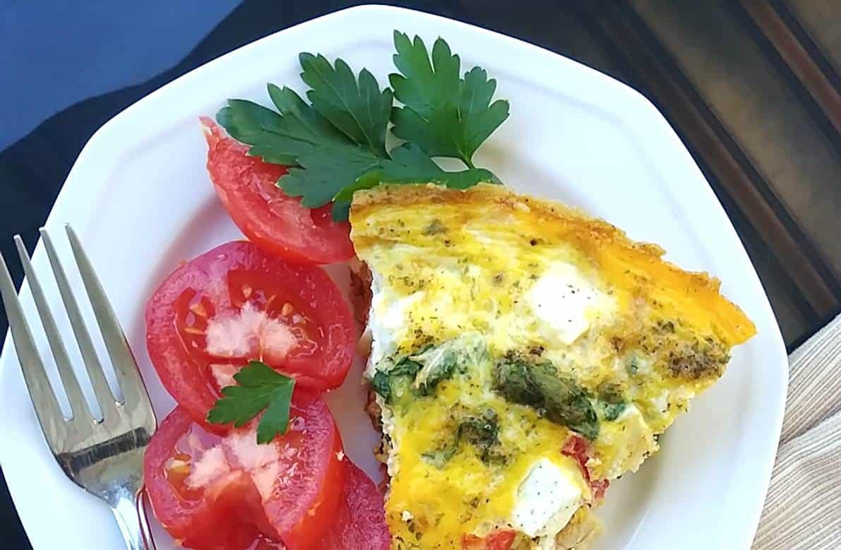 Pointe d'omelette au fromage sur assiette blanche avec tomates vue de haut