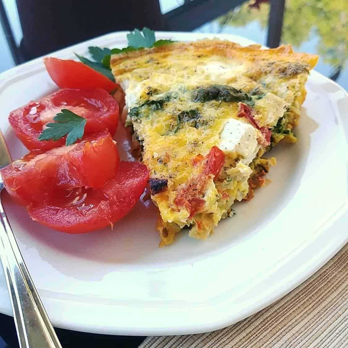 Photo d'une pointe découpée de l'omelette servie avec tomates et persil plat.
