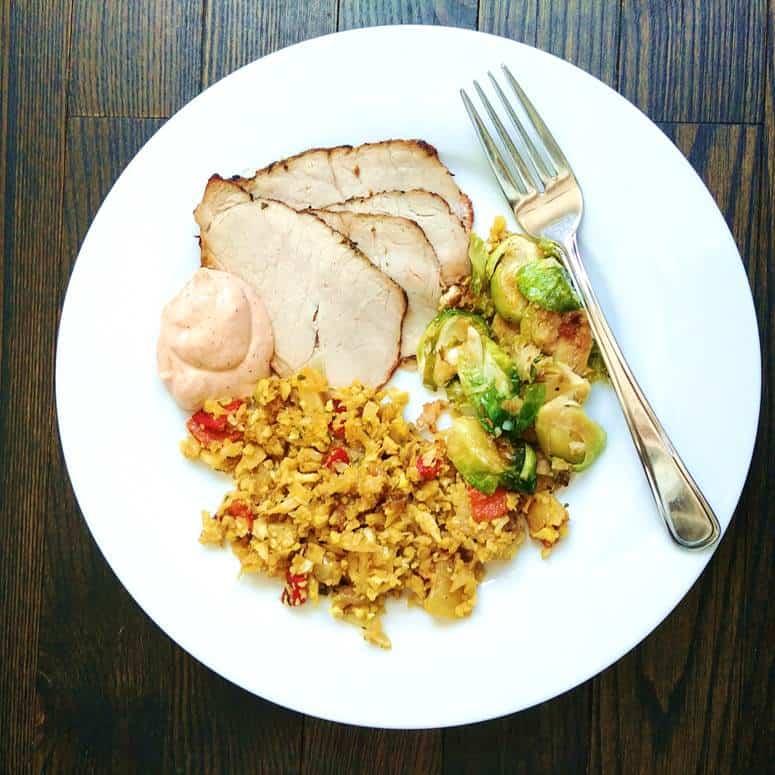 Assiette de porc à l'ail avec mayo, choux de bruxelles et riz frit de chou fleur au cumin sur planche de bois foncé.