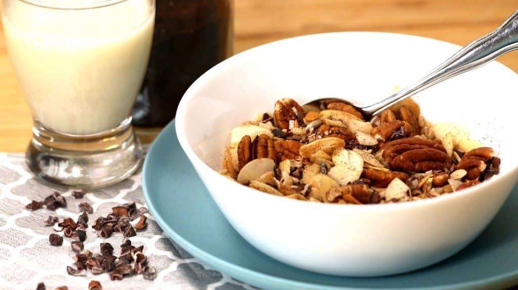 Bol de céréales sans sucre vue de côté avec les fèves de cacao et le verre de lait d'amandes