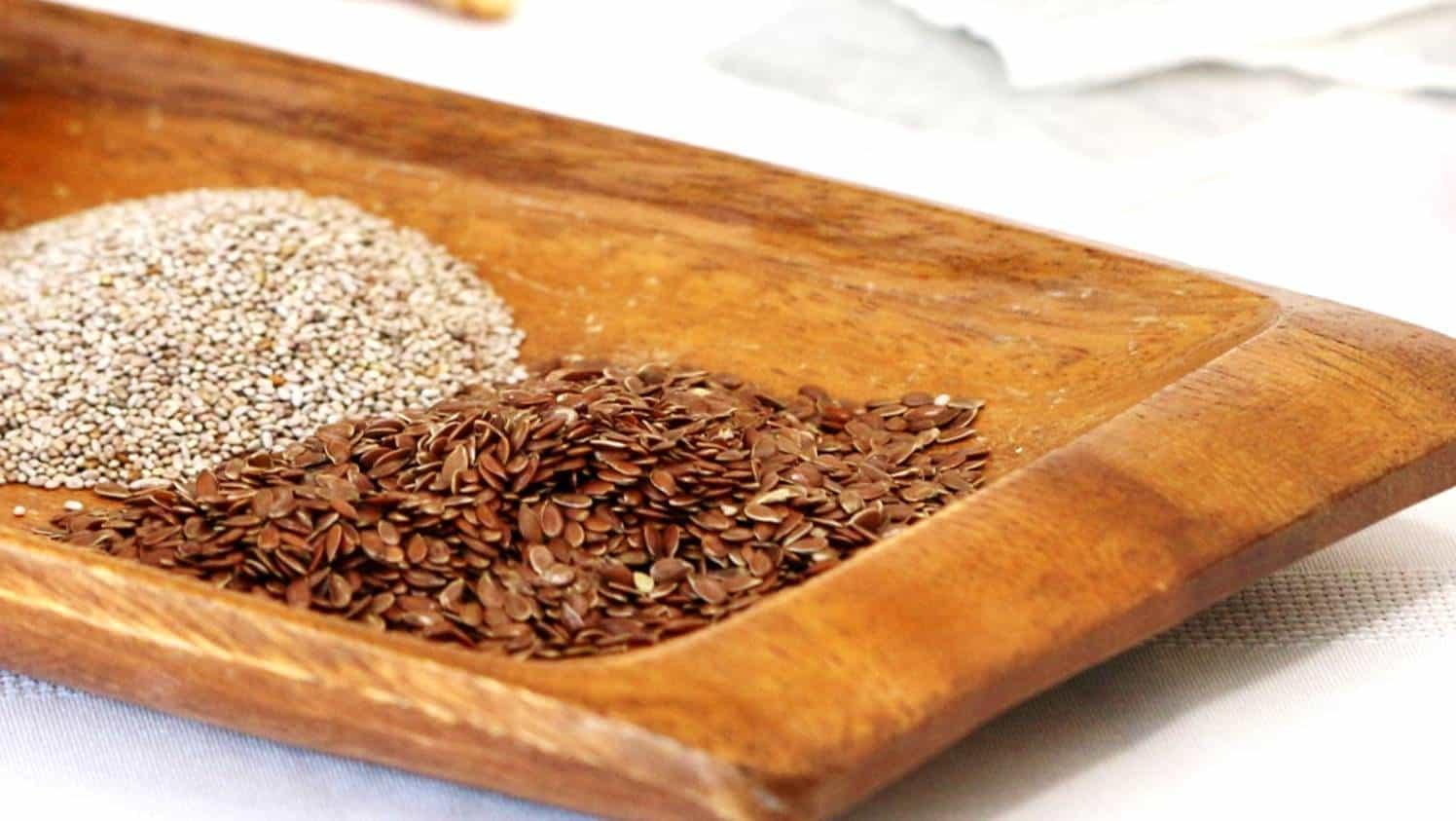 plateau en bois avec des graines de lin et de chia blanches