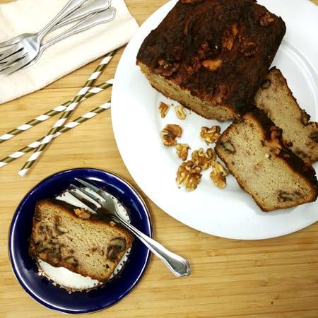 Vue de haut d'une assiette du pain aux noix et citrouille tranché, déposé sur une planche de bois.