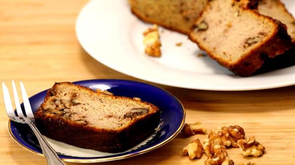 Photo d'une tranche de pain sans gluten aux noix et citrouille dans une petite soucoupe bleu royal sur planche de bois.