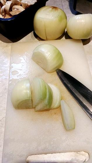 Planche à découper avec un oignon en languettes