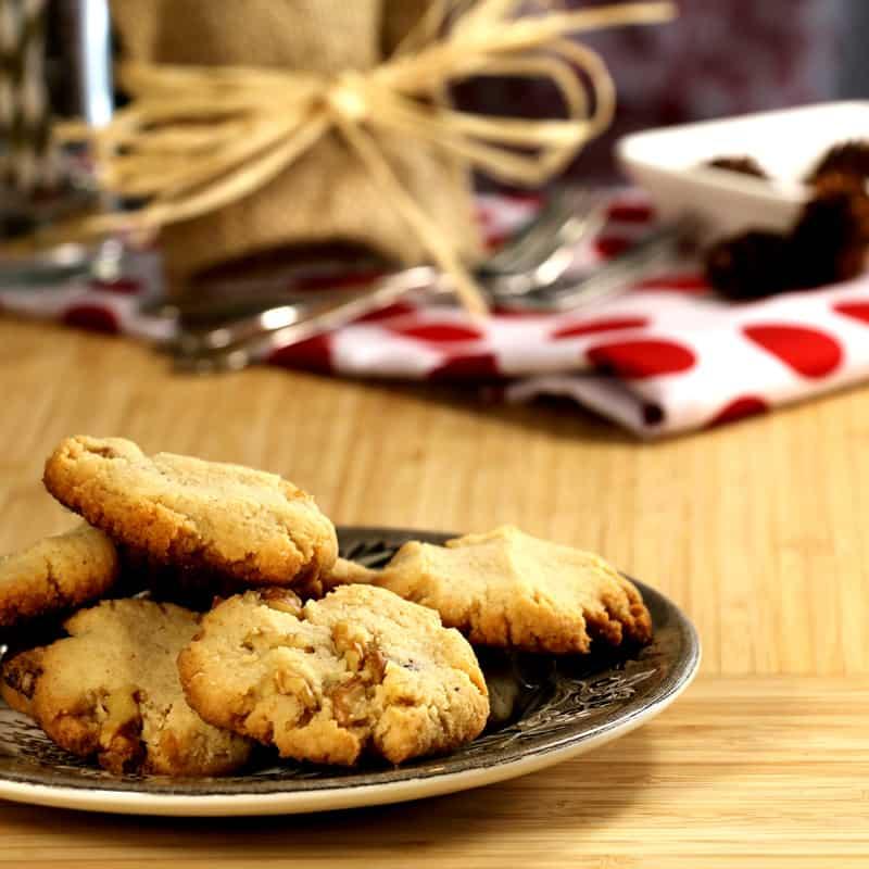 Assiette de biscuits aux noix de Grenoble sans sucre sur planche de bois.