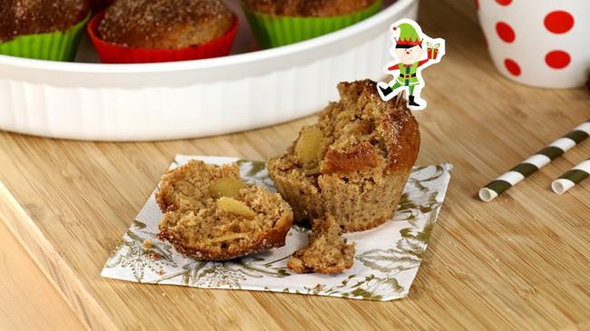 Muffin de Noël séparé en deux pour voir la texture moelleuse sur une serviette de table blanche avec fleurs de couleur dorée