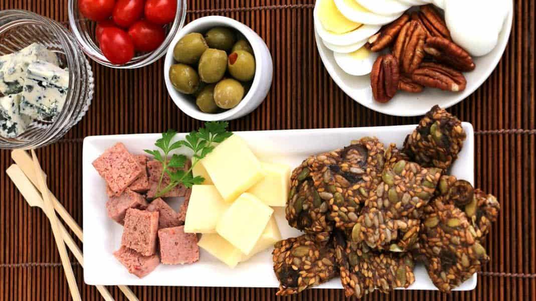 Assiette de la recette de craquelins maison avec fromage, noix, olives, pâté et tomates.