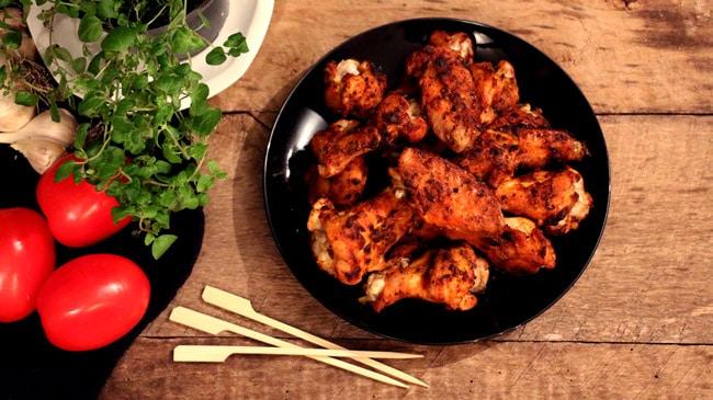 ailes de poulet sur assiette noire et planche de bois avec petits pics en bois