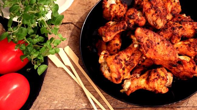 Assiette d'ailes cuites sur planche de bois avec tomates et un petit plant d'origan