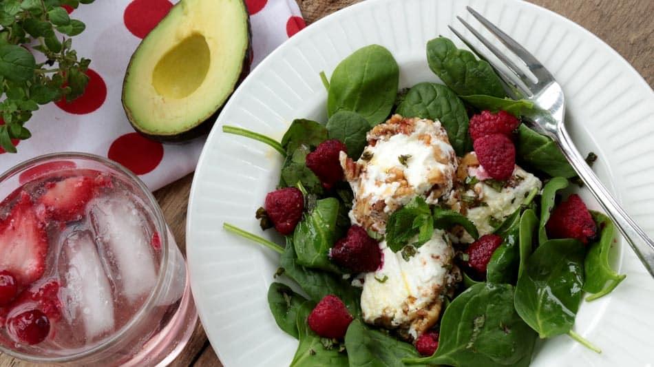 Assiette de salade de chèvre chaud aux noix avec avocat et eau pétillante