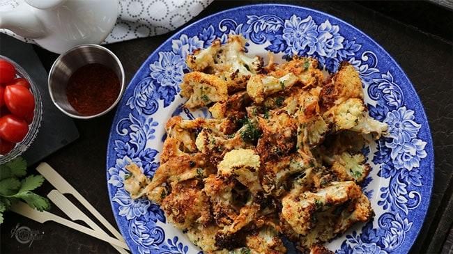 assiette bleu royal avec chou-fleur rôti et gratiné sur plateau brun