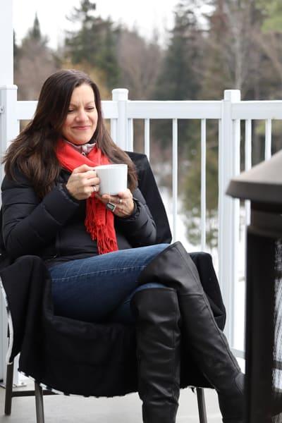 Johanne buvant une tasse de tisane près du foyer extérieur en hiver