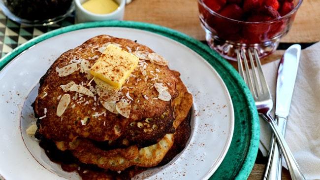 Une petite pile de pancakes sur une assiette avec un gros carré de beurre et du coconut râpé
