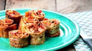 rouleaux de pizza sur assiette turquoise sur planche de bois