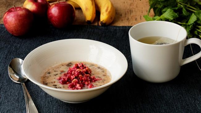 Bol de gruau sans gluten avec tisane et fruits en arrière-plan