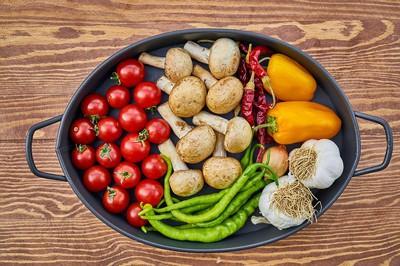 Casserole remplie de légumes sur planche de bois vue de haut