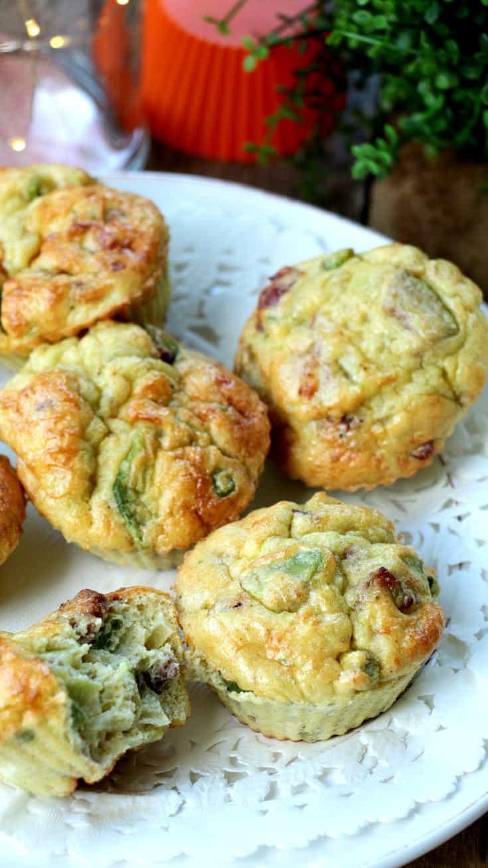 Muffins salés sur une assiette blanche dont un qui est croqué en deux