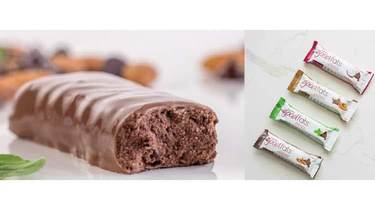 Une barre love good fats coupée en deux et les emballages sur marbre