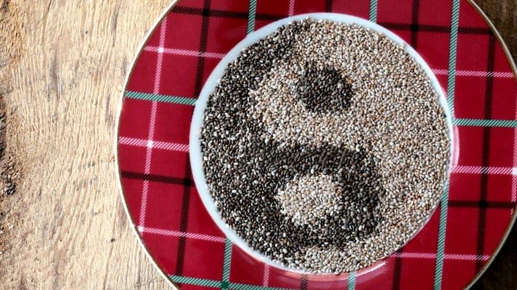 Graines de chia blanches et noires dans une assiette disposées en signe de ying et yang, graines riches en fibres