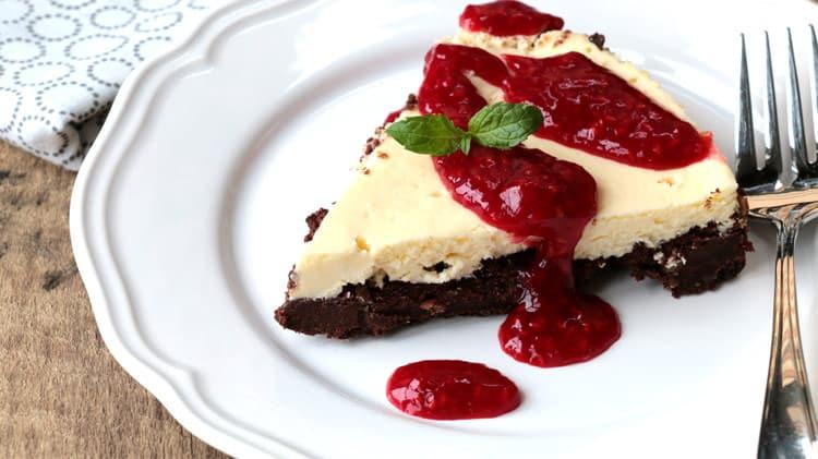 Vue de près d'une pointe de gâteau au fromage et chocolat avec coulis de framboises