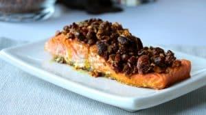 Saumon en croûte de noix sur assiette blanche vu de côté