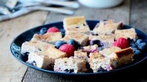 Bouchées de gâteau au fromage et et petits fruits sur assiette bleu et planche de bois